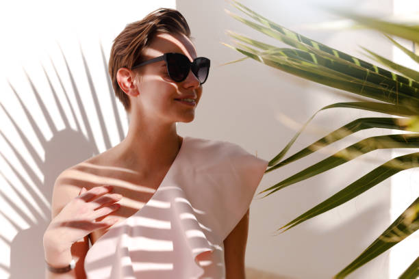 mädchen steht im schatten der palme in einem schönen kleid. das foto vor der weißen wand an einem sonnigen tag gemacht. mädchen trägt ein rosa kleid und großen sonnenbrillen. - modedetails stock-fotos und bilder