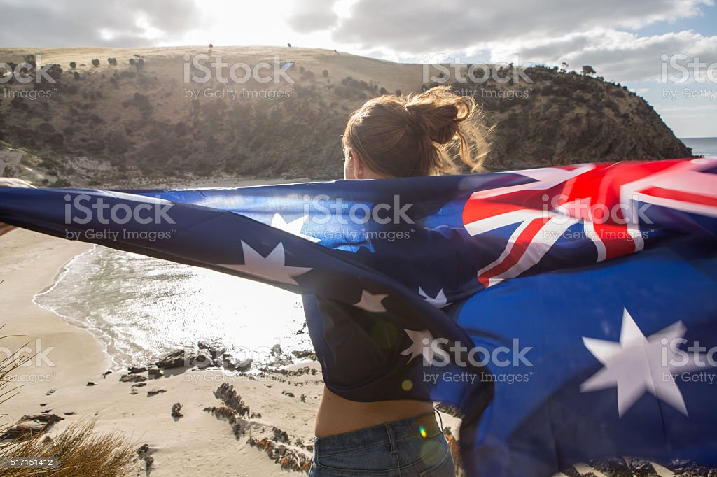 Girl stands on cliff above beach holding Australian's flag stock photo