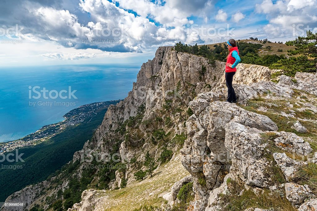 Girl stands on the edge of the cliff stock photo