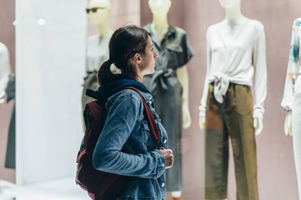 Mädchen steht vor dem Laden und schaut auf die weibliche Kleidung auf den Schaufensterpuppen. – Foto