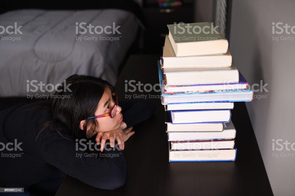 Meisje van staren naar reus stapel boeken op Bureau - Royalty-free Alleen kinderen Stockfoto