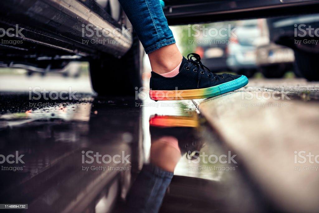 Chica saliendo del coche y evitando el Charco - Foto de stock de Adolescente libre de derechos