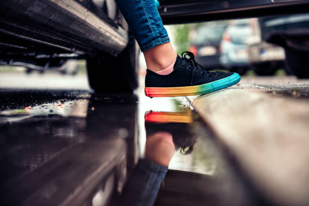 Girl stepping out of the car and avoiding puddle Girl wearing black sneakers stepping out of the car and avoiding puddle stepping stock pictures, royalty-free photos & images