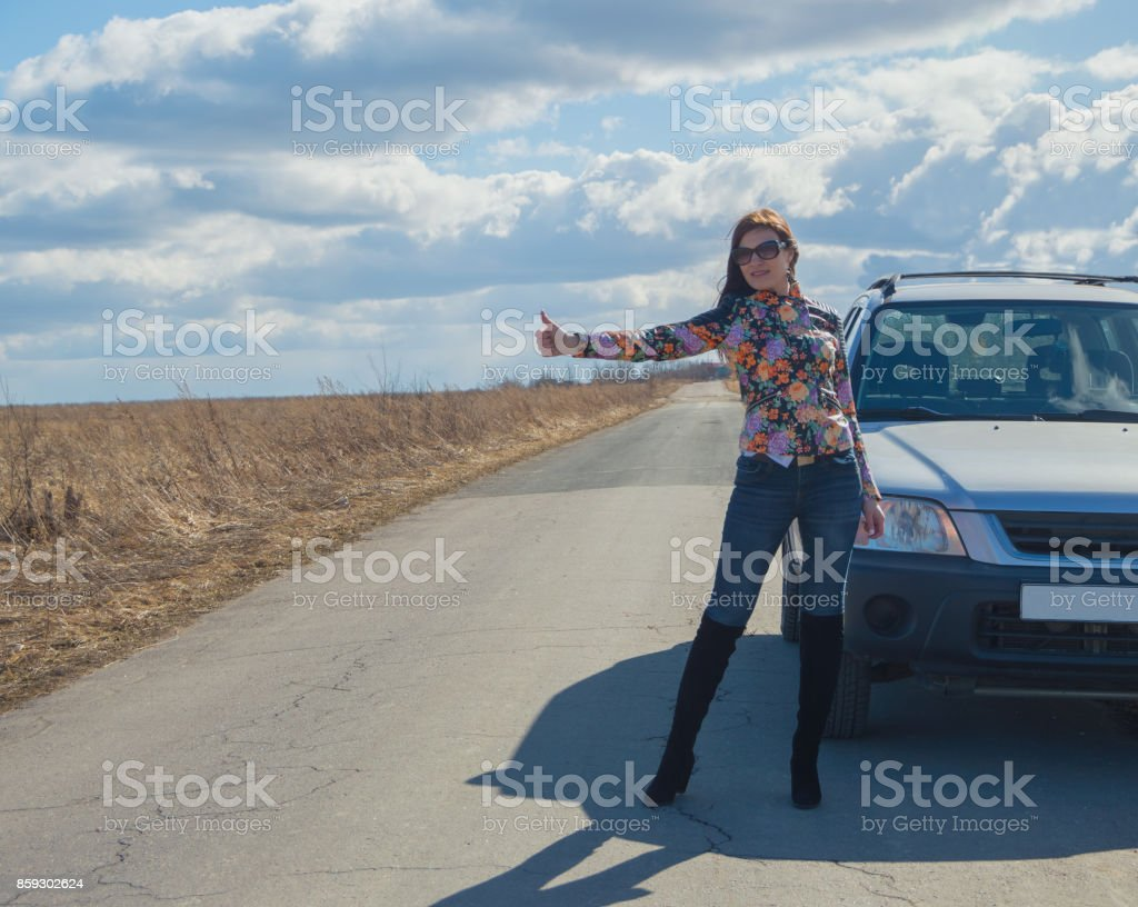 girl stops the car, raising his hand on a deserted road stock photo