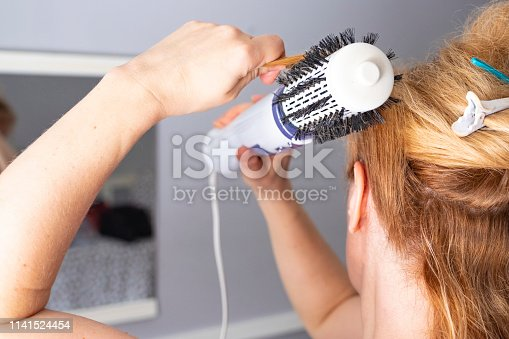 istock Girl straightens hair with a Volumebrush brush-dryer. European white woman with dyed hair in red color. 1141524454