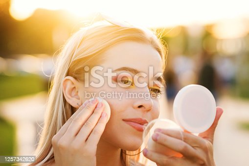 Stylish girl straightens bright makeup on the street. A young woman uses compact powder and looks in the mirror. Backstage. Close-up portrait in the sunset light. Hot summer evening