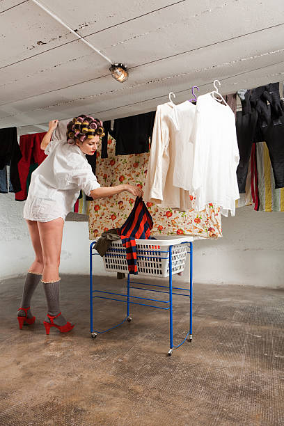 girl stretches clothes in the room girl housewife stretches clothes in the basement append stock pictures, royalty-free photos & images