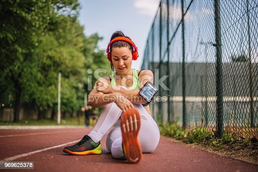 520047182istockphoto Girl stretches on the track and listening music 969625378