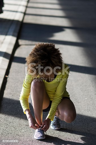 520047182istockphoto Girl stretching and listening to the music on her headphones 520046300