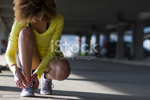 520047182istockphoto Girl stretching and listening to the music on her headphones 520046704