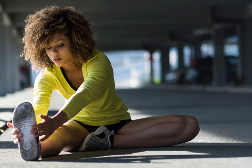 istock Girl stretching and listening to the music on her headphones 520047182