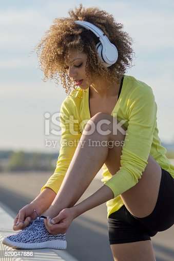 520047182istockphoto Girl stretching and listening to the music on her headphones 520047686