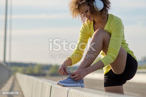 520047182istockphoto Girl stretching and listening to the music on her headphones 520048176