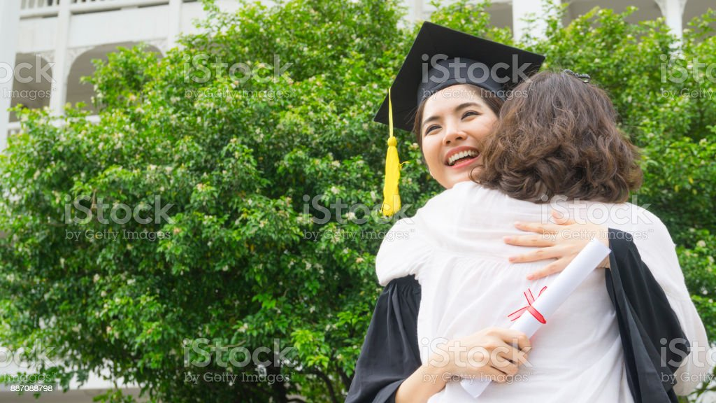 girl student with the Graduation gowns and hat hug the parent in congratulation ceremony. stock photo