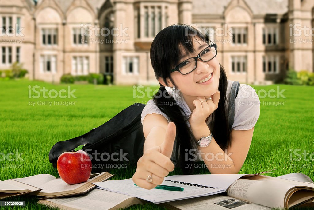 Girl studying and lying at school yard royalty-free stock photo