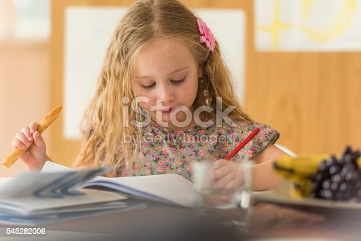 Close-up of girl holding breadstick and studying at home.