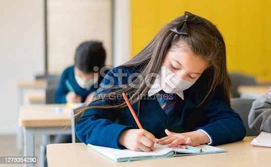 Girl studying at the school wearing a facemask during the COVID-19 pandemic - back to school concepts