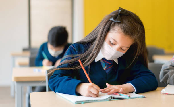 Girl studying at the school wearing a facemask during the pandemic stock photo