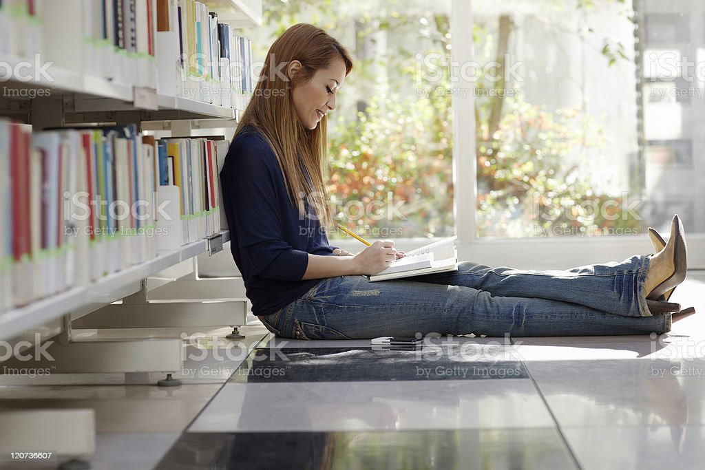 girl studying on floor in library royalty-free stock photo
