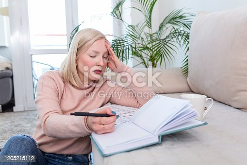 1057767656 istock photo Girl studying the day before the exam, writing notes with a pencil. Pretty young girl doing her studies at home sitting on the floor in the living room with a book reading a binder of class notes 1205215112