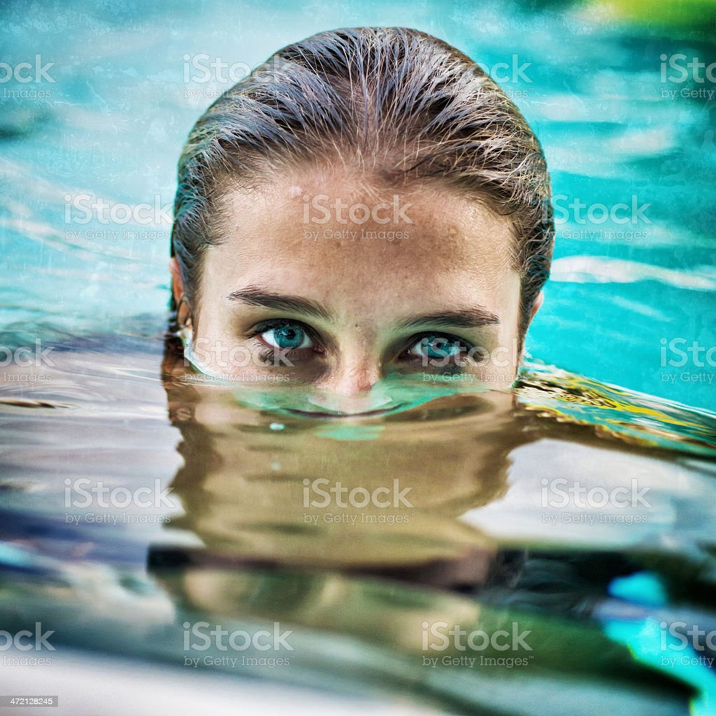 Girl submerged underwater with her eyes above the water stock photo