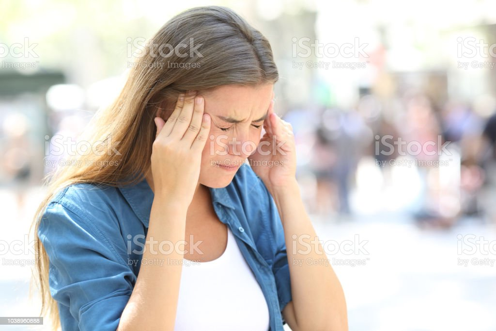 Girl suffering migraine in the street stock photo