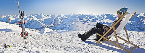 Girl sunbathing in a deckchair near a snowy ski slope Panorama of a girl sunbathing in a deckchair near a snowy ski slope ski holiday stock pictures, royalty-free photos & images