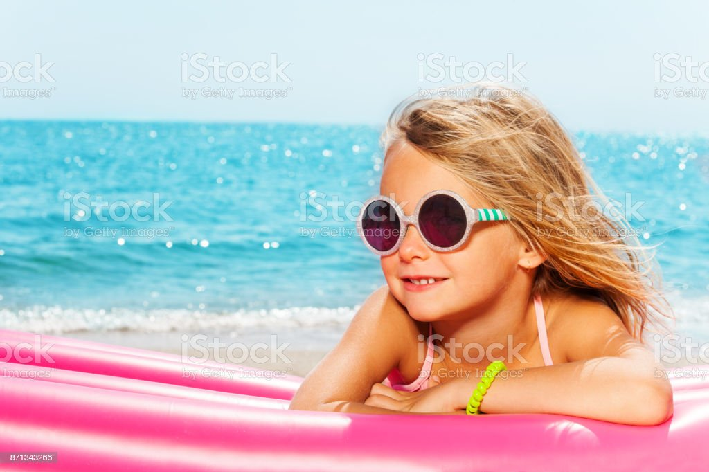 Girl sunbathing on inflatable lounge by the sea stock photo