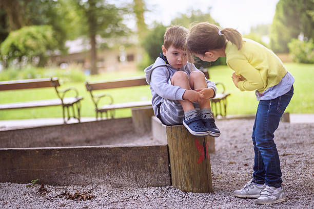 girl supporting sad boy sitting alone - comfort stock photos and pictures