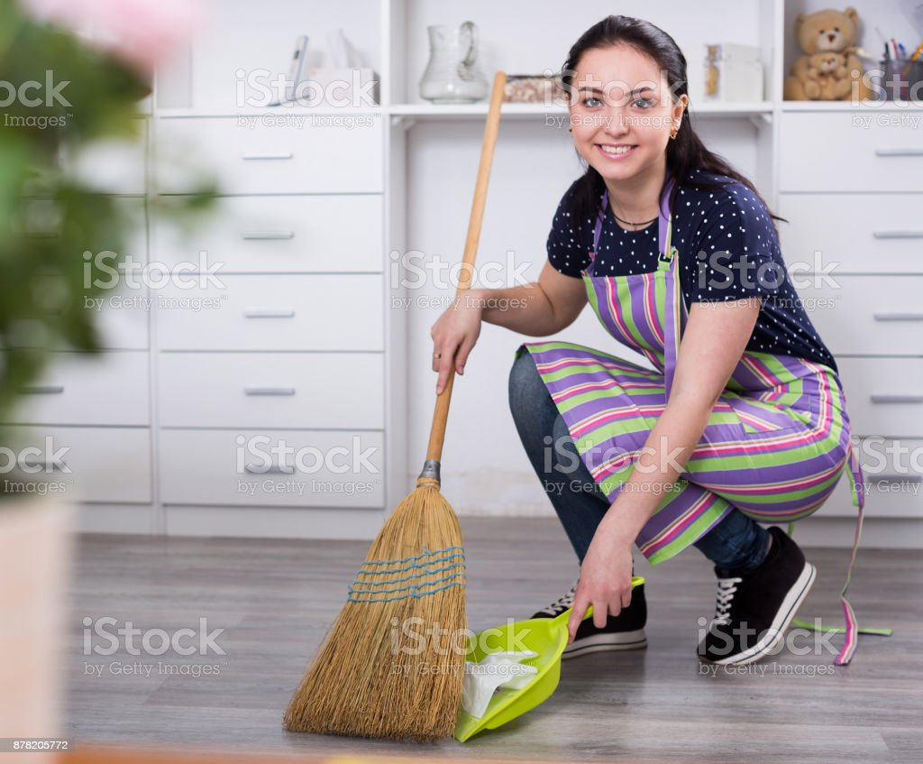 Girl sweeping garbage stock photo
