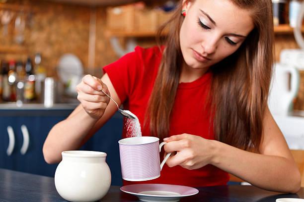 girl sweetening her tea or coffee stock photo