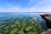 A girl swims in Lake Superior in the upper peninsula of Lake Michigan. Rocks are visable through the glass like, pristine waters. Pictured Rocks National Lakeshore is in the distance.
