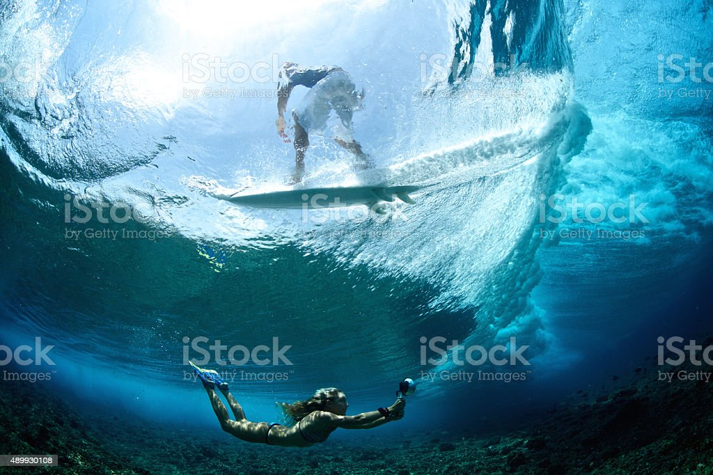 Girl swims under a wave that surfer rides stock photo