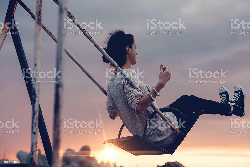 Girl swinging at sunset stock photo