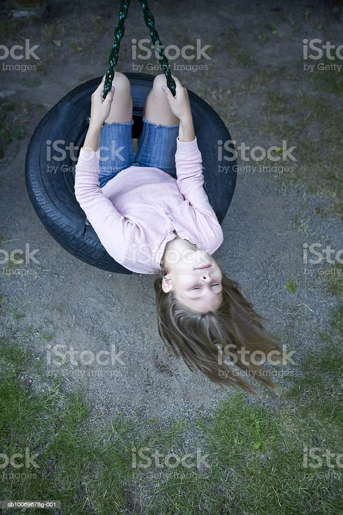 Girl (8-9) swinging on tire swing, high angle view foto de stock libre de derechos
