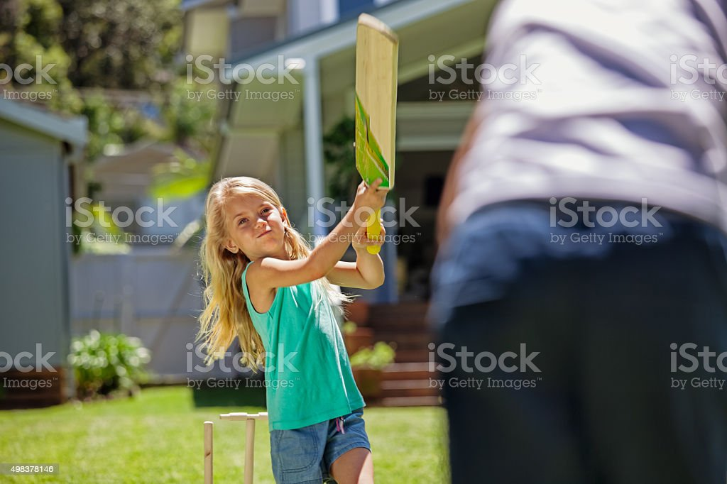 girl swings at bat in game of cricket stock photo