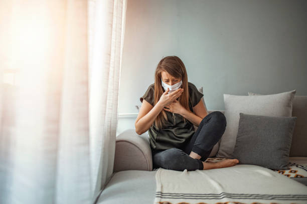 Girl symptom cough while sitting on Sofa. Coronavirus. Woman wearing surgical mask on face protective for spreading of disease Covid-19 pandemic.. Girl symptom cough while sitting on Sofa. Sick woman in face protection mask mucus stock pictures, royalty-free photos & images