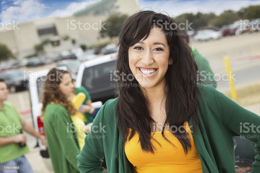 Girl tailgating with other college students at football stadium royalty-free stock photo
