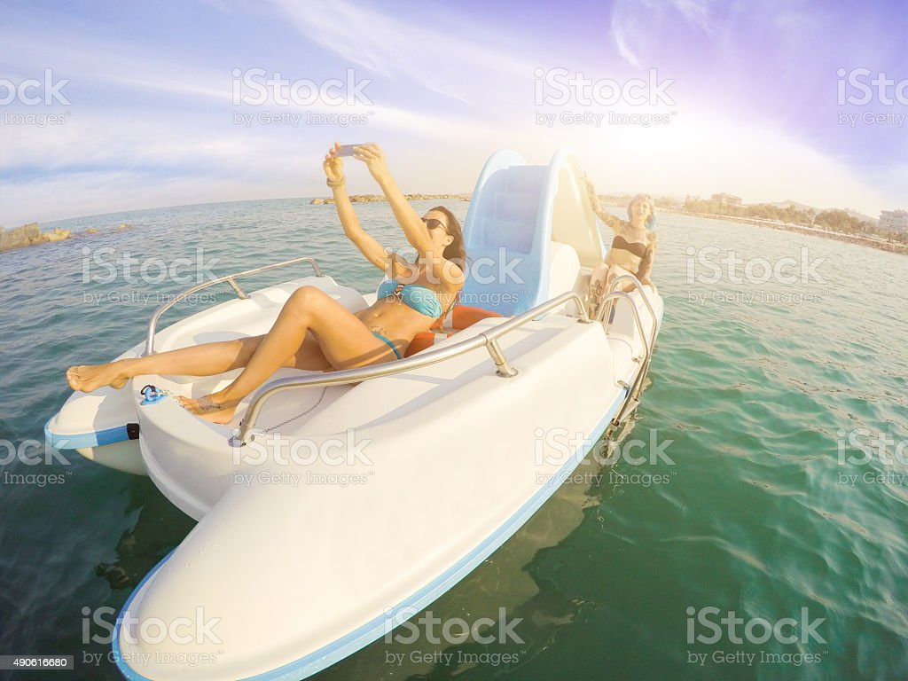 Girl take selfie on boat in summertime stock photo
