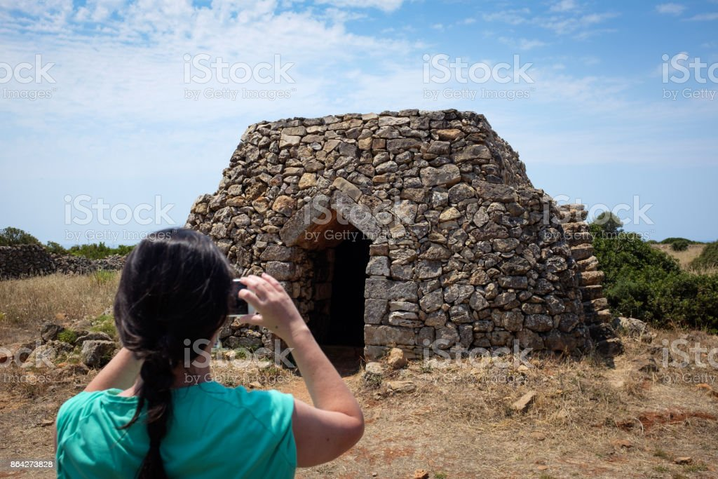Girl takes a photo of a typical Apulian stone house named Trullo royalty-free stock photo