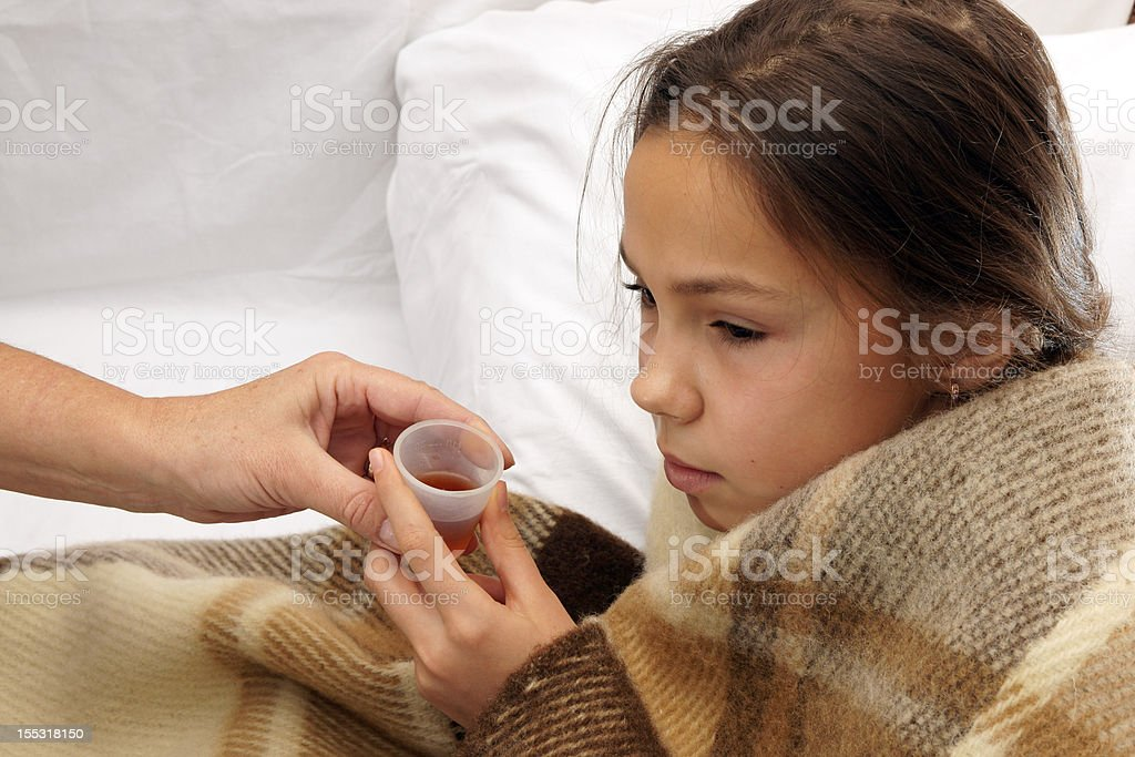 Girl takes medicine stock photo