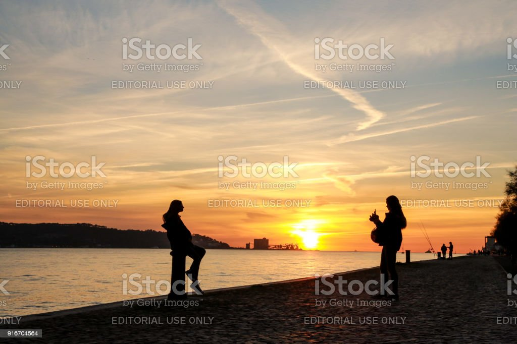 Girl takes photo of another, with mobile phone, at a beautiful sunset, Lisbon, Portugal, stock photo