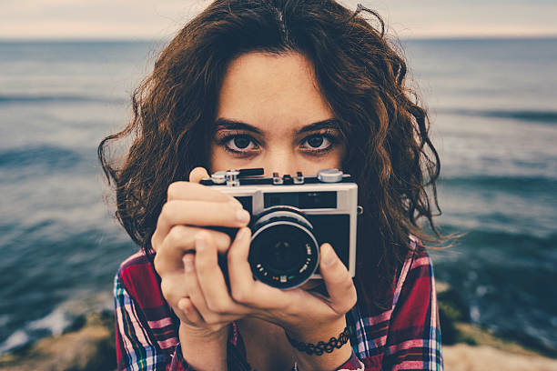 girl taking a photo at sea with a film camera - vintage stock photos and pictures