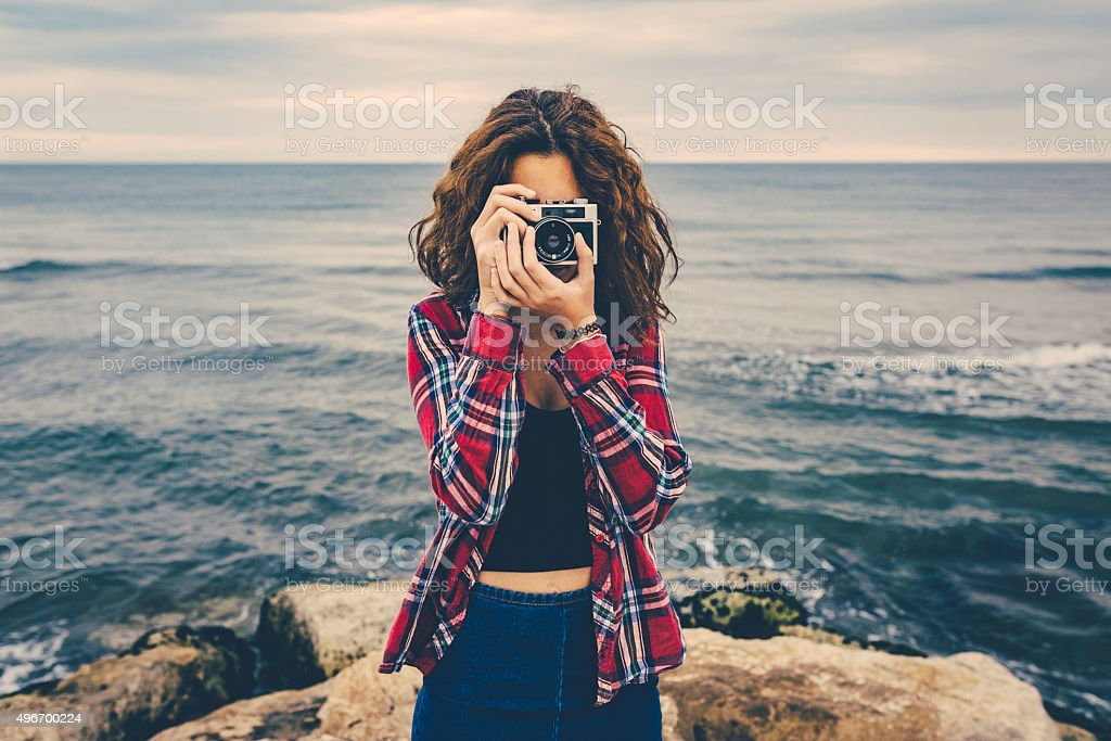 Girl taking a photo at sea with a film camera Girl taking a photo at sea with a film camera 2015 Stock Photo