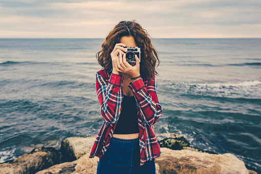 Girl Taking A Photo At Sea With A Film Camera Stock Photo - Download Image Now