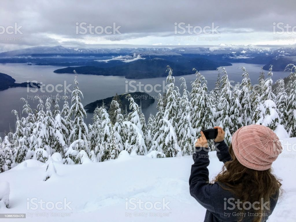 A girl taking a picture atop Cypress Mountain overlooking the ocean below stock photo