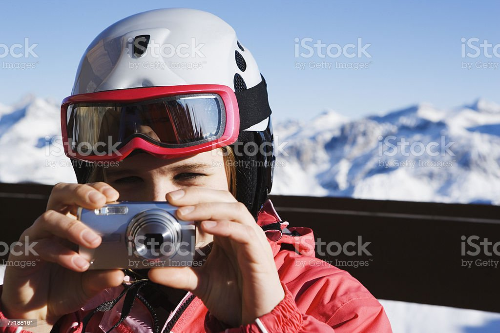 A girl taking a picture outdoors in the snow royalty-free stock photo
