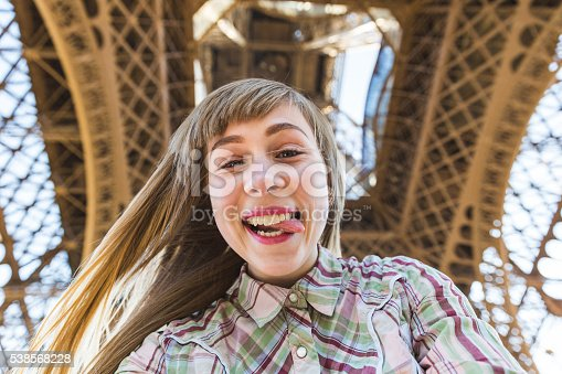 Beautiful blonde girl taking a selfie under the Eiffel Tower in Paris. She is looking at camera, smiling and grimacing with the tongue out of the mouth. Travel and lifestyle concepts.