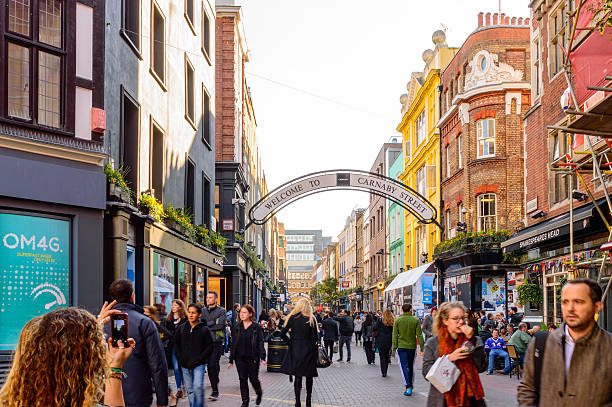Girl taking a smartphone picture of Carnaby Street, London London, England - October 26, 2015: A girl taking a smartphone picture of Carnaby Street - which looks very busy full of shoppers. carnaby street stock pictures, royalty-free photos & images