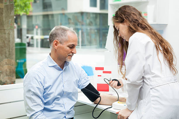 Girl taking blood pressure to mature man stock photo